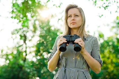 A woman observes surroundings having binoculars, sunset sun in back ground