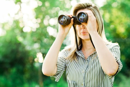 A woman looks through binoculars outdoor in forest before sunset