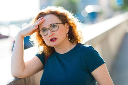 Attractive woman on street feeling sudden head ache - discomfort gesture Standard-Bild - 124697465