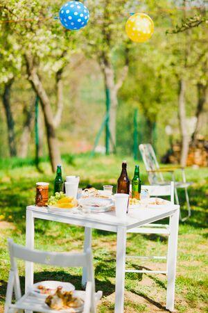 Mesa pequeña con botellas de cerveza y comida en fiesta en el jardín de verano