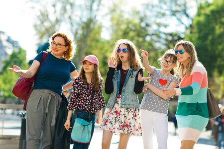 Group of girls pointing to interesting places, mothers and daughters together on a trip in downtown Imagens