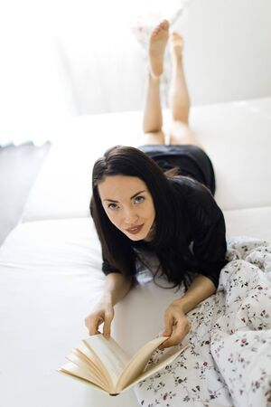 Attractive woman dressed in black sleepwear laying on bed in the morning and reading book