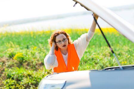 A woman in orange vest open car bonnet of broken car - trying to solve problem Reklamní fotografie