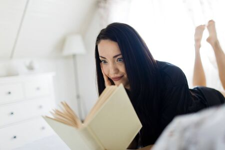 A woman dressed in black sleepwear laying on bed reading book - having rest