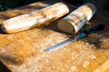 Bread and knife on wooden board, outdoor picnic food