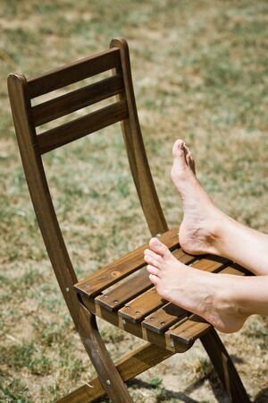 Womans foot on brown wooden chair outdoor Stock Photo
