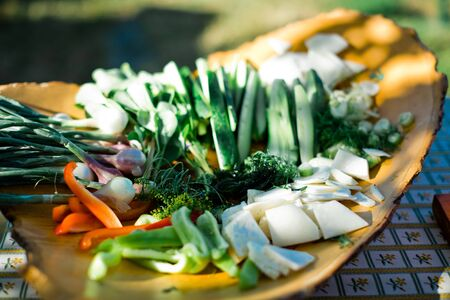 Fresh vegetable on wooden plate with sliced healthy products