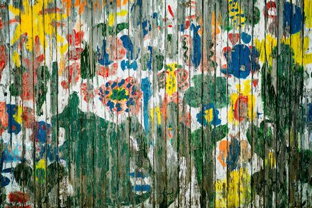 Old colorful wooden fence with cracked old paining, textured background