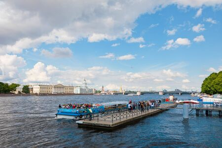 St. Petersburg, Russia - July 7, 2019: Tourist waiting at quayside to have boat trip on Neva river Редакционное