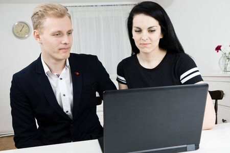 Superiors works with subordinate. Blond man working with black haired woman, disputing emotionally