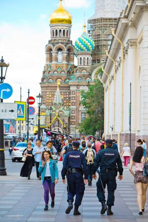 St. Petersburg, Russia - July 8, 2019: Two policemen walking to Church of the Savior on Spilled Blood Редакционное