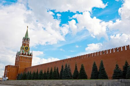 Moscow, Russia - July 9, 2019: Brick wall and Spasskaya Tower of Kremlin on Red Square Редакционное