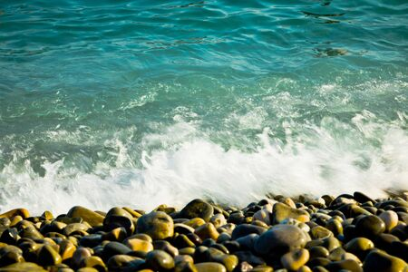 Motion of wave splashed on Rounded rocks on beach, motion blur