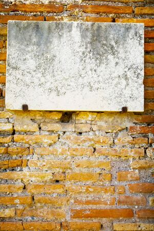 Vintage marble sign on brick wall, patina on surface