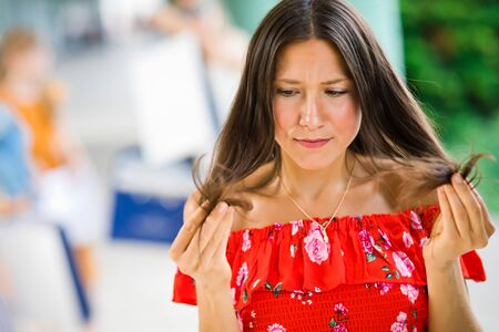 Young woman in red dress looking at destroyed hair ends, hairstyle or better shampoo needed Foto de archivo