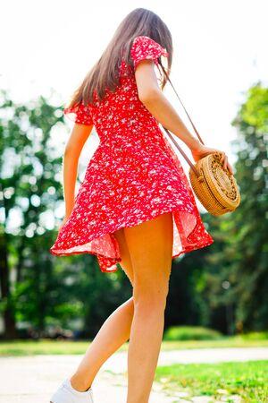 Vista dal basso verso l'alto sulla giovane donna che posa in abito rosso, gambe naturalmente attraenti del modello nel parco