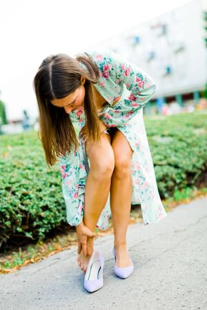 Elegant woman feeling foot ache, wearing small shoes or using high heel for long time