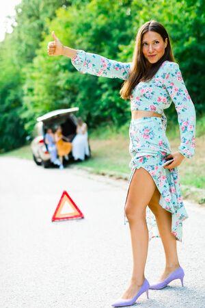 Sexy woman seduce as hitch-hiker trying to catch car showing her leg, having broken car