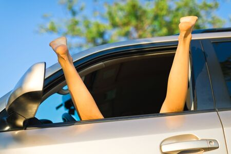 Prostitute with spread out legs exposed out of window of car, feet