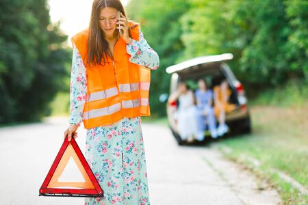 Woman in orange reflective vest installing red warning triangle on the road and calling, children and broken car in background