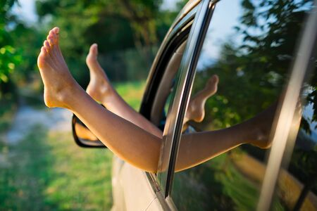 Prostitute with spread out legs exposed out of window of car, side view