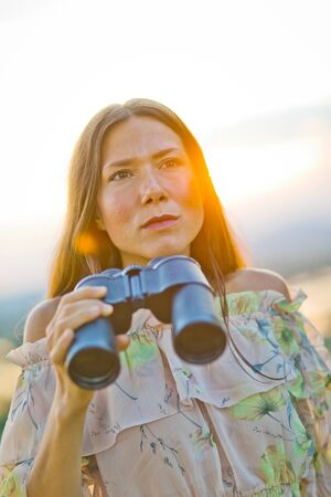Woman in summer dress holding binoculars, looking to distances