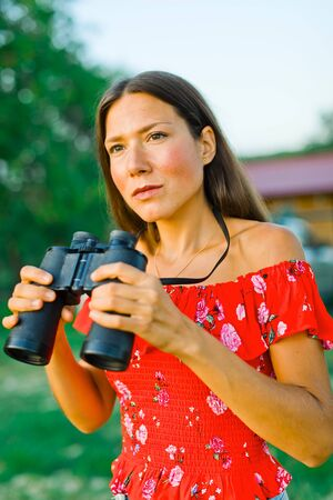 Woman in red dress and short jeans skirt going to use binoculars