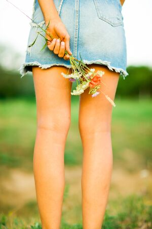 Young womans legs from back and bouquet of meadow flowers