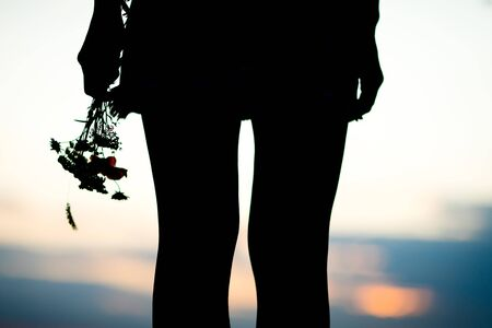 Young womans legs and bouquet of meadow flowers, silhouette against sunset