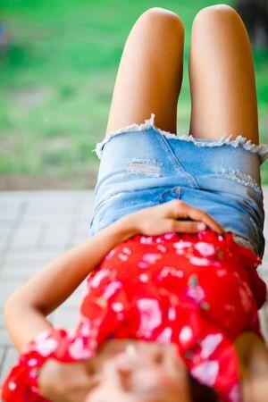 Thigh of girl in short jeans skirt lying outside