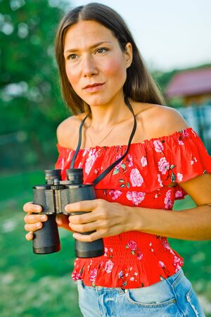 Woman in red dress and short jeans skirt holding binoculars Фото со стока