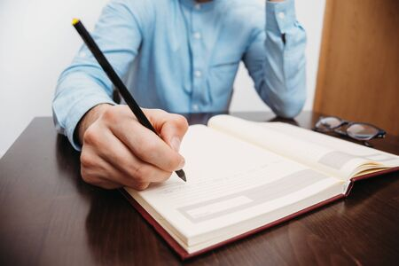 Man writing hand on book in the office Stock Photo