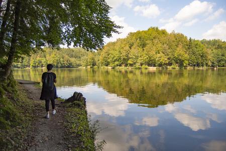 Woman walking by the lake on a beautiful sunny day, Croatia