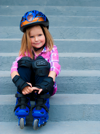 patines: girl in roller skates sitting on stairs