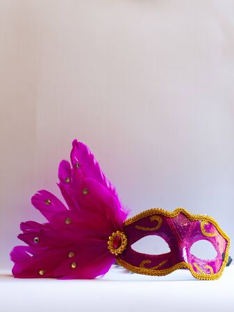 Pink eye mask with feathers on white background