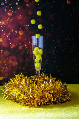 A glass of champagne with several lucky grapes levitating. New Years Celebration 2021