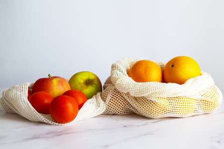 Different fruits and vegetables on a white table, inside a cloth bag. Concept of sustainable shopping and purchasing without plastics. Copy Space