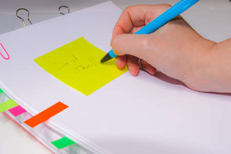 Close-up of a hand writing on a yellow paper. Horizontal photography. Information overload concept