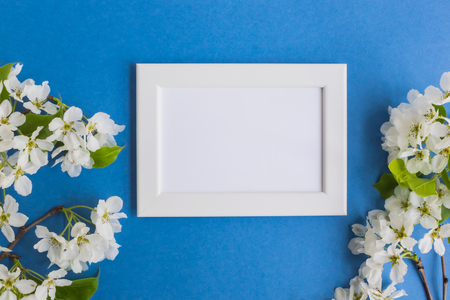 Mockup With A White Frame And White Spring Flowers On A Blue