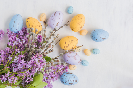 Easter eggs and lilac branches on a light background