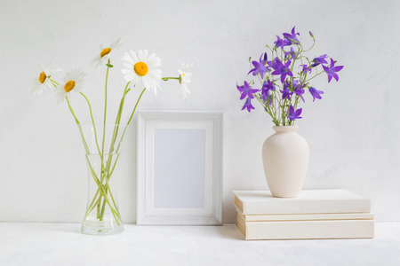 Home interior with decor elements. White frame, flowers in a vase, books and pencils