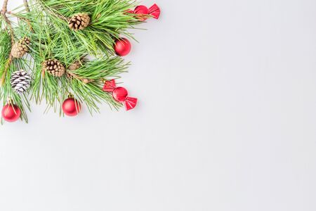 Holiday background with christmas branches and balls on a light background