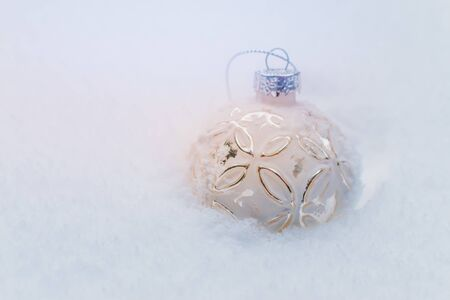 Glass ball on white snow. Christmas and New Year holidays background