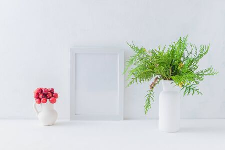 Mockup white frame and christmas branches in a vase on a light background