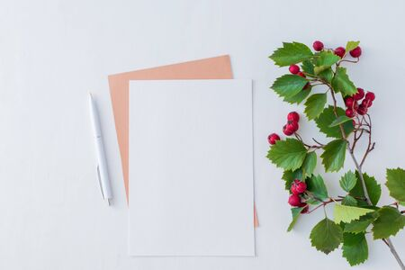 Mockup blank paper card and branch with red berries on a white background. Flat lay, top view