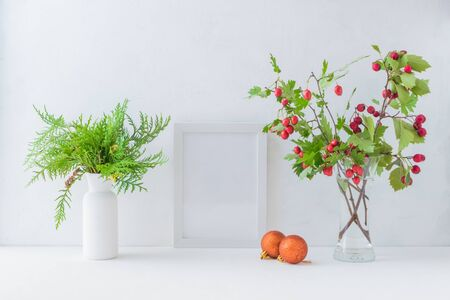 Mockup white frame and branches with red berries in a vase on a light background Stock Photo - 130803627