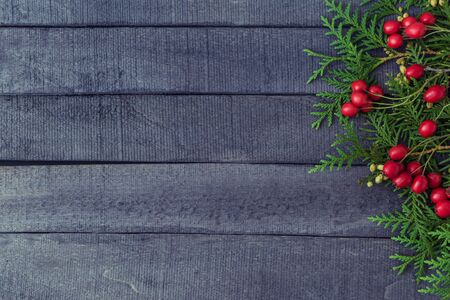 Holiday background with christmas branches and decoration on a dark wooden background