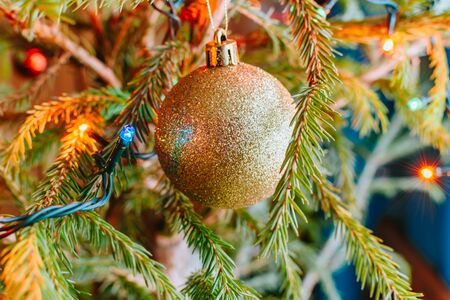 Festive background with christmas ball and garland hanging from fir branches