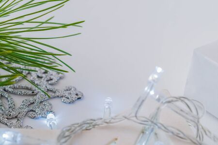 Holiday composition with christmas pine branches and a garland on a light background Stock Photo