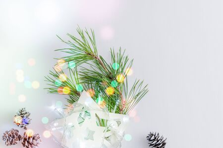 Holiday composition with christmas pine branches and a garland on a light background Фото со стока